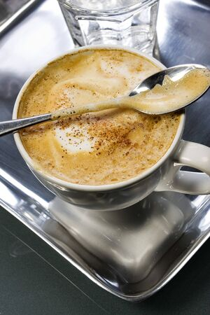 capuccino: Capuccino in a white cup with glass of water Stock Photo