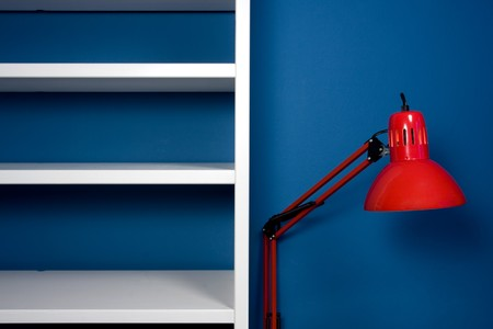 White empty bookcase with red reading lamp in blue room