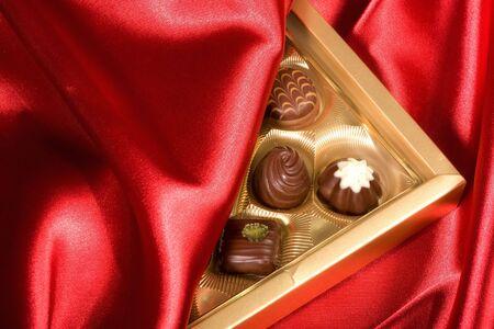 dainty: Golden chocolates box on red satin background Stock Photo