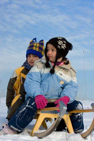 Little girl and boy on sleigh photo