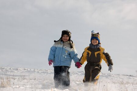 Little girl and boy running through the snow. Stock Photo