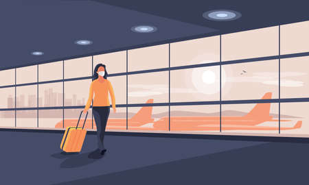 Lonely business woman traveler wearing face mask with luggage walking at empty airport gate terminal lounge traveling during pandemic outbreak. Airplanes behind glass window with city skyline sunset.