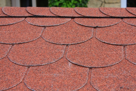 Red asphalt shingle roofing on a roof Stock Photo