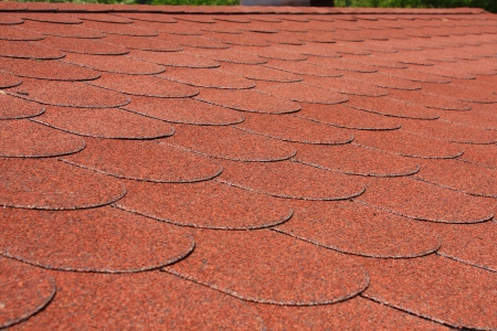 tar felt: Red asphalt shingle roofing on a roof Stock Photo