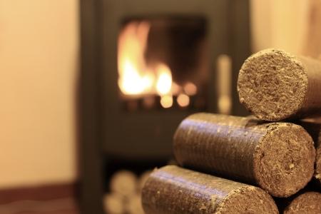 holzbriketts: Holzbriketts für Kaminöfen Hintergrund mit Feuer Lizenzfreie Bilder