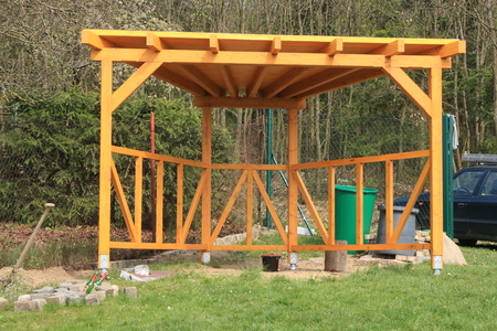Wooden pergola painted yellow glazing, built in the garden of the house
