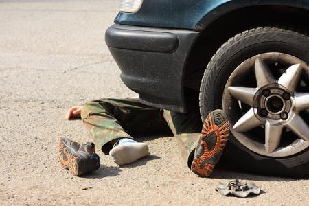 事故 - のブートを選択する車の車輪の下で小さな少年