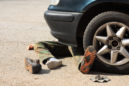 car body: Accident - A small boy under the wheels of a car to pick on boot