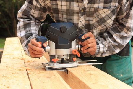 Carpenter milled wood upper hand electric router photo