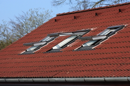 Three white open skylights on the roof with brown concrete roofing photo