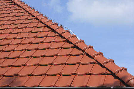 roof ridge: The new roof is covered with red burnt roof tiles and ridge tiles Stock Photo