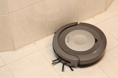 sucks: Small robotic vacuum cleaner sucks up tiles in the bathroom Stock Photo