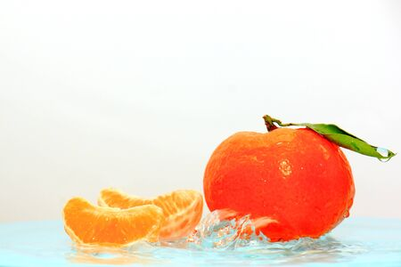 Orange tangerine with a green leaf in wavy water