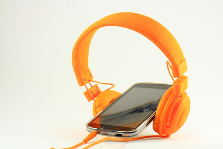 Orange headphones and mobile phone with a scratched screen Reklamní fotografie