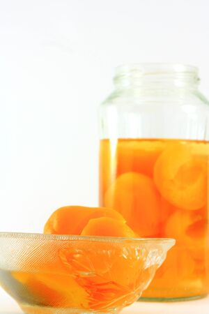 Canned apricots in a glass bottle and a glass bowl