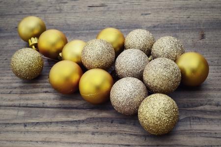 Golden christmas balls on a wooden background Standard-Bild