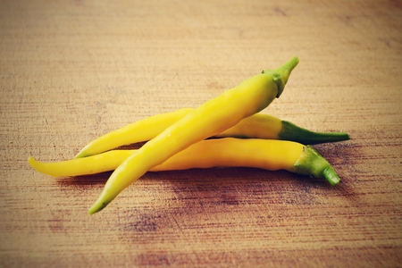 Yellow chili pepper on wooden background