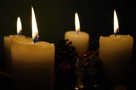 white candles in front of a black background