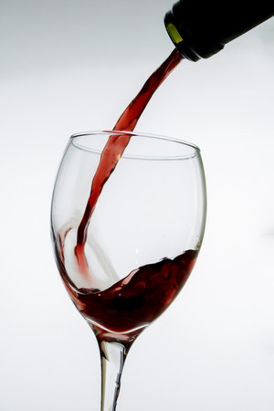 Pouring red wine into a glass. Liquid, scented. Concentrates body of the red wine pouring into the wine glass an image isolated on white Banco de Imagens - 113775339