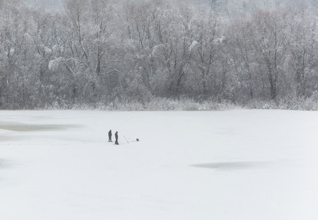 The river is covered with ice and covered with snow. Two people catch fish on winter fishing. On the opposite shore trees in the snow