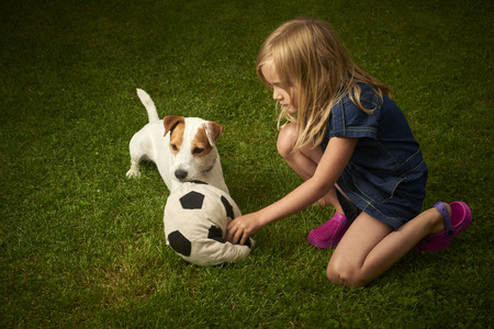 Cute little blond girl playing with her dog