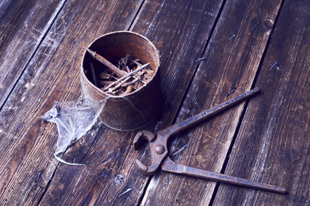 holdfast: Old rusty can of pinchers with nails on wooden boards background