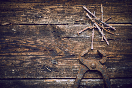 holdfast: Old rusty tongs with nails on wooden boards background
