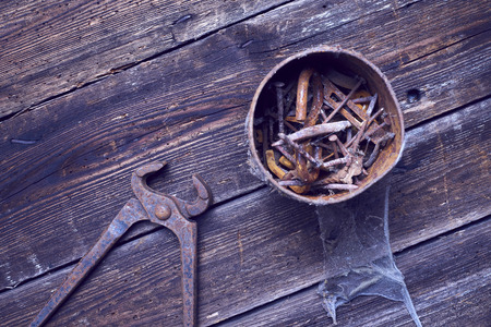 holdfast: Old rusty can of pinchers with nails on wooden boards Stock Photo