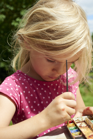 A girl painting with water colors (watercolors) painting a paper plate with watercolor paints outside in garden