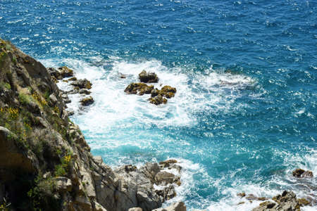 Sea rocks and waves in beautiful sunny day