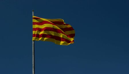 Flag of Catalonia against a blue sky