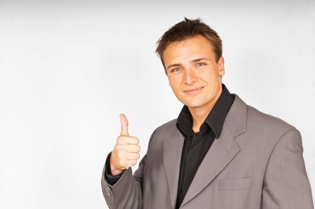 Young attractive man in suit shows the thumb up Stock Photo - 7389529