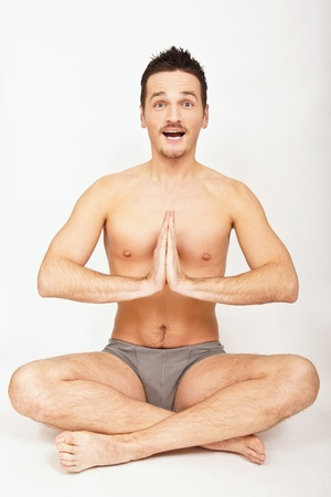 Young man is making yoga on the light background.  Stock Photo - 8497527
