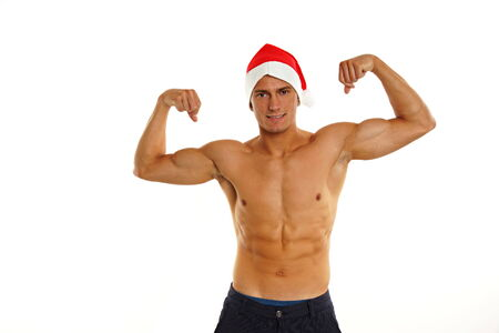 Atletic bronzed sexy Santa Claus poses on white background photo