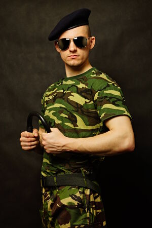 nightstick: Young military man holds nightstick at hand