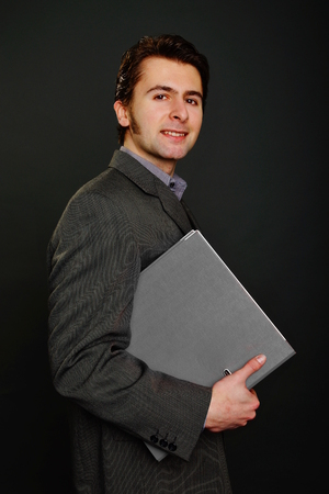 worktops: Young man at suit holds gray worktops Stock Photo