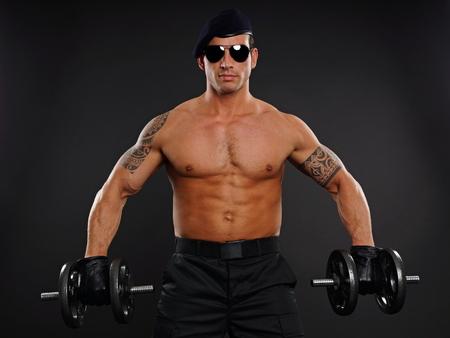 militaire sexy: Portrait de soldat musculaire � lunettes de soleil tenant des halt�res Banque d'images