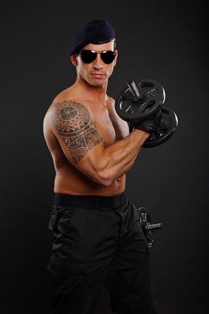 militaire sexy: Soldat des exercices avec halt�res biceps et les poses