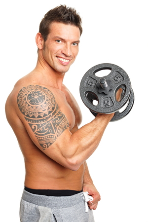 Handsome muscular man exercises with dumbbell biceps photo