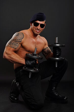 Muscular soldier kneeling on one knee posing with dumbbells photo