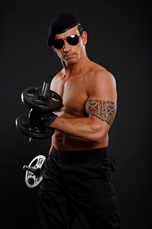 Soldier exercises biceps and poses with dumbbells  photo