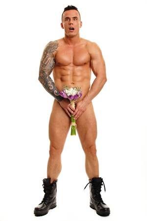 Handsome naked muscular man poses with bouguet of tulips photo