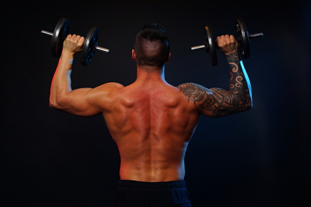 Young man standing exercises with dumbbells and shows muscular back photo