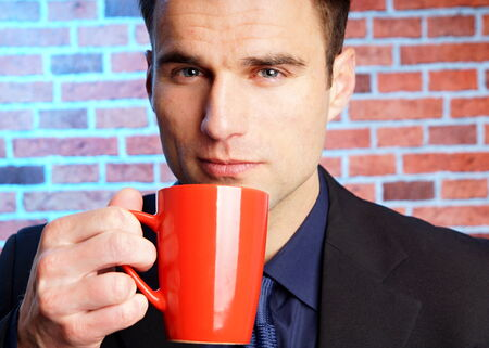 tractive: Handsome businessman in suit drinking cup of coffee