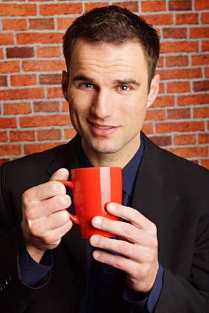 tractive: Handsome businessman in suit holds cup of coffee