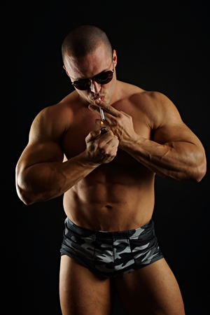 Muscular man in sunglasses ignited cigarette on the dark background photo