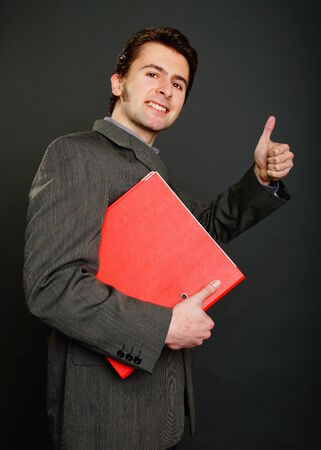 worktops: Young man in suit holds worktops and shows you thumb up on gray background