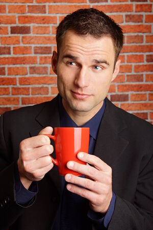 tractive: Thinking businessman in suit holds cup of coffee Stock Photo