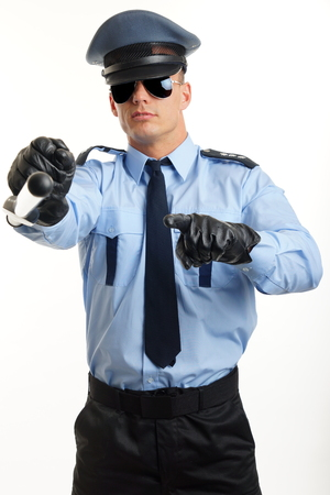 Young man in police uniform shows on you with nightstick Stock Photo