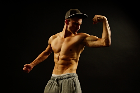 Young athlete man poses on dark background photo